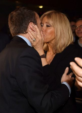 French presidential election candidate for the En Marche movement Emmanuel Macron kisses his wife, Brigitte Trogneux, as he arrives for a campaign rally on March 9, 2017 in Talence, southwest France. / AFP PHOTO / MEHDI FEDOUACH