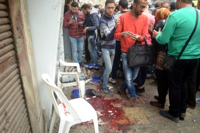 Egyptians look at the scene after suicide bomber in front of a church in Alexandria