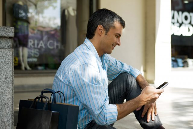 Man sitting with outdoors with shopping bags, using cell phone --- Image by © Sandro di Carlo Darsa/PhotoAlto/Corbis