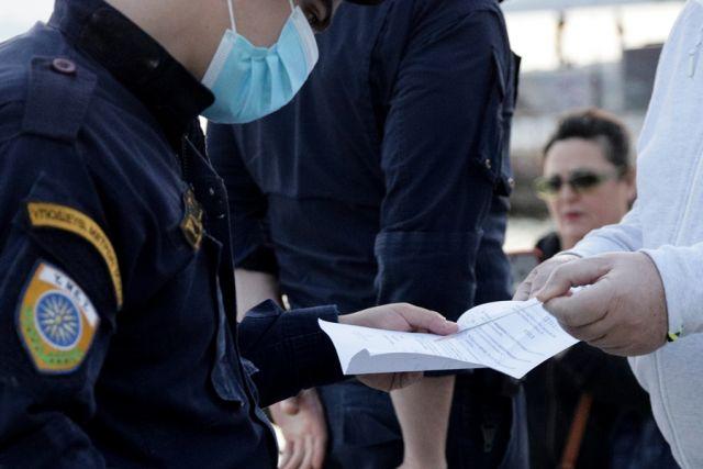 Αστυνομικός κοιτά το χαρτί βεβαίωσης της κυκλοφορίας