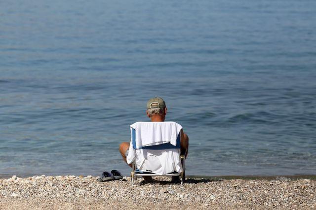 Άνδρας σε καρέκλα παραλία