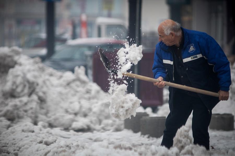 Άνδρας μαζεύει το χιόνι