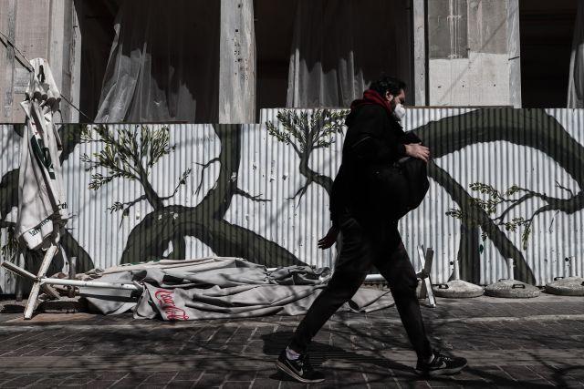 Άνδρας με μάσκα περπατάει